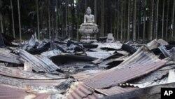 Bức tượng Phật nằm giữa cảnh hoang tàn của một ngôi chùa gần biên giới Bangladesh và Miến Điện bị hàng ngàn người Hồi giáo Bangladesh phóng hỏa thiêu rụi