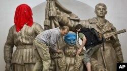 Pendukung Pussy Riot memakaikan penutup wajah pada patung monumen Perang Dunia Kedua di Moskow sebagai bentuk protes terhadap vonis penjara bagi para anggota band Pussy Riot.