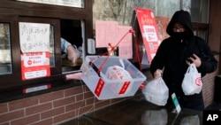 Un hombre recoge bolsas de su pedido de alimentos mientras un trabajador lo coloca en una canasta para evitar el contacto humano después del brote de coronavirus, en Beijing, el domingo 23 de febrero de 2020.