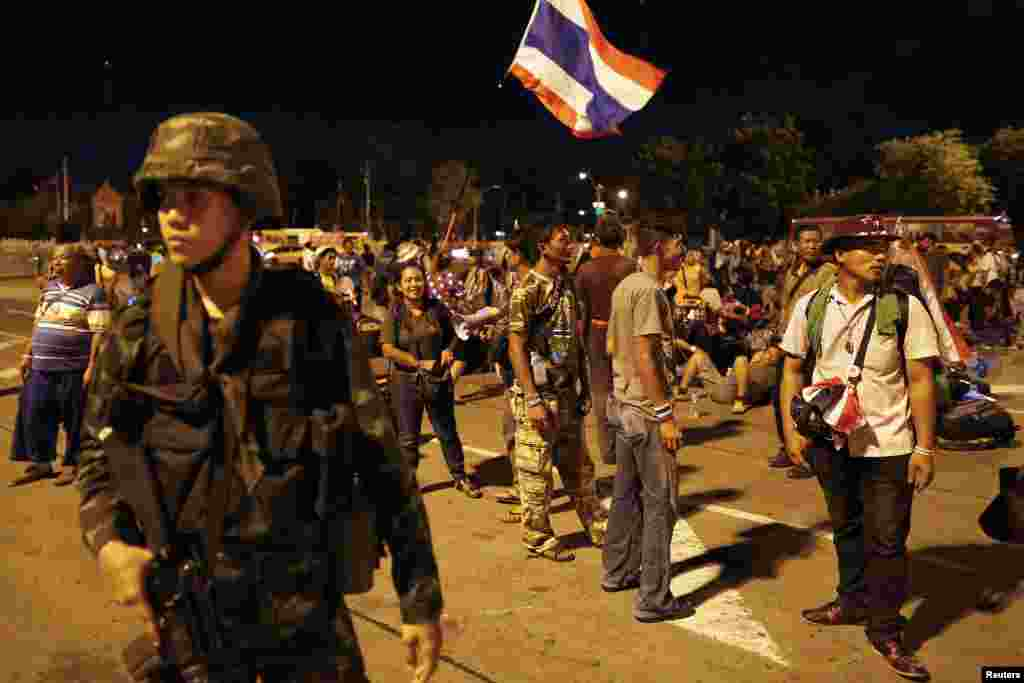 Anti-government protesters waiting at the Royal Plaza for transportation home stand behind a soldier after the coup was declared in Bangkok, May 22, 2014.