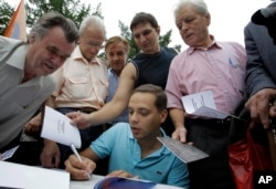 FILE - Vladimir Milov, a leader of the Democratic Choice party, signs autographs during a rally of party's supporters in Moscow, June 25, 2011.