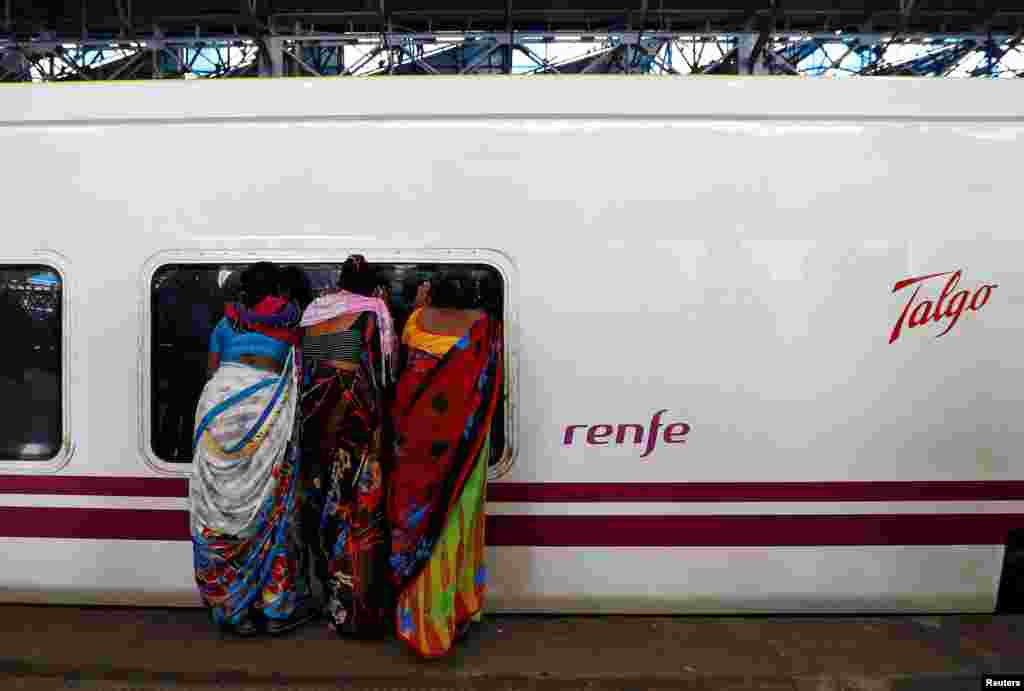 People look inside the parked high speed Talgo train during its trial run at a railway station in Mumbai, India.