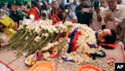 FILE - In this July 11, file photo, the body of Cambodian government critic Kem Ley is covered by the Cambodian National flag as flowers are placed during a funeral ceremony in Phnom Penh, Cambodia. Oeut Ang, the man who allegedly shot dead Kem over what