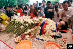 FILE - In this July 11, file photo, the body of Cambodian government critic Kem Ley is covered by the Cambodian \flag as flowers are placed during a funeral ceremony in Phnom Penh, Cambodia.