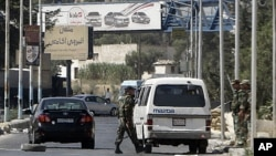 Syrian soldiers man a checkpoint at the entrance of Harasta northeast of the capital Damascus, August 29, 2011
