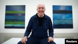 """Artist Sean Scully poses with his works """"Landline Bruke 5.14"""" (L) and """"Landline Blue Blue"""" at the Timothy Taylor Gallery in London, Nov. 20, 2014."""