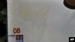 有人在北京办理护照的机构外面手持新护照,上面的地图显示南中国海属于中国