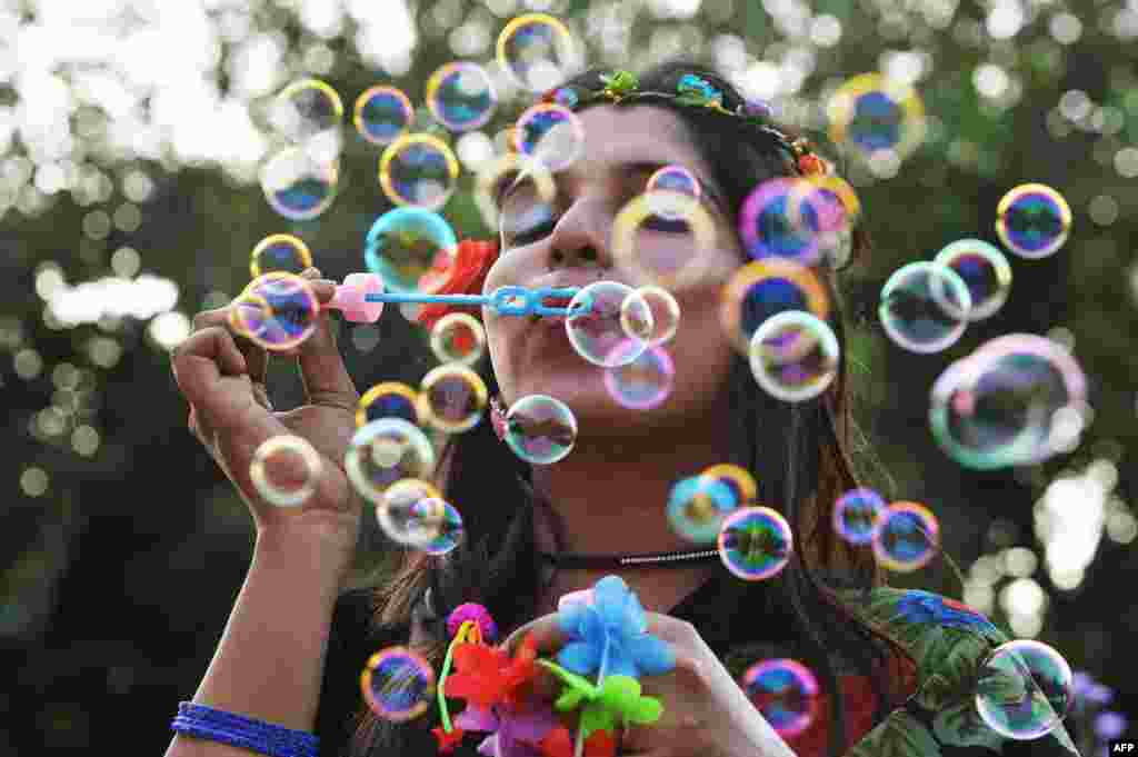 An Indian transgender activist blows bubbles during the annual Bengaluru Pride march in Bangalore . The annual march is aimed at ending violence and opression based gender identity and sexual orientation.