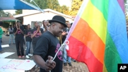 FILE - Samba Chesterfield, Director of Gays and Lesbians Association of Zimbabwe, prepares to hoist their official flag alongside the Zimbabwean flag during an event in Harare, Zimbabwe, May, 19, 2012.