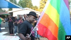 FILE: Samba Chesterfield, Director of Gays and Lesbians Association of Zimbabwe, prepares to hoist their official flag alongside the Zimbabwean flag during an event in Harare, Zimbabwe, May, 19, 2012.