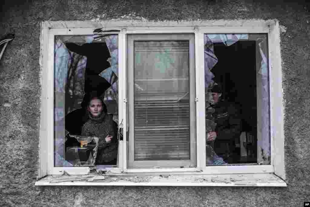 A Ukrainian woman looks through a broken window after it was hit by Ukrainian artillery, near Donetsk, Ukraine, Jan. 18, 2015.