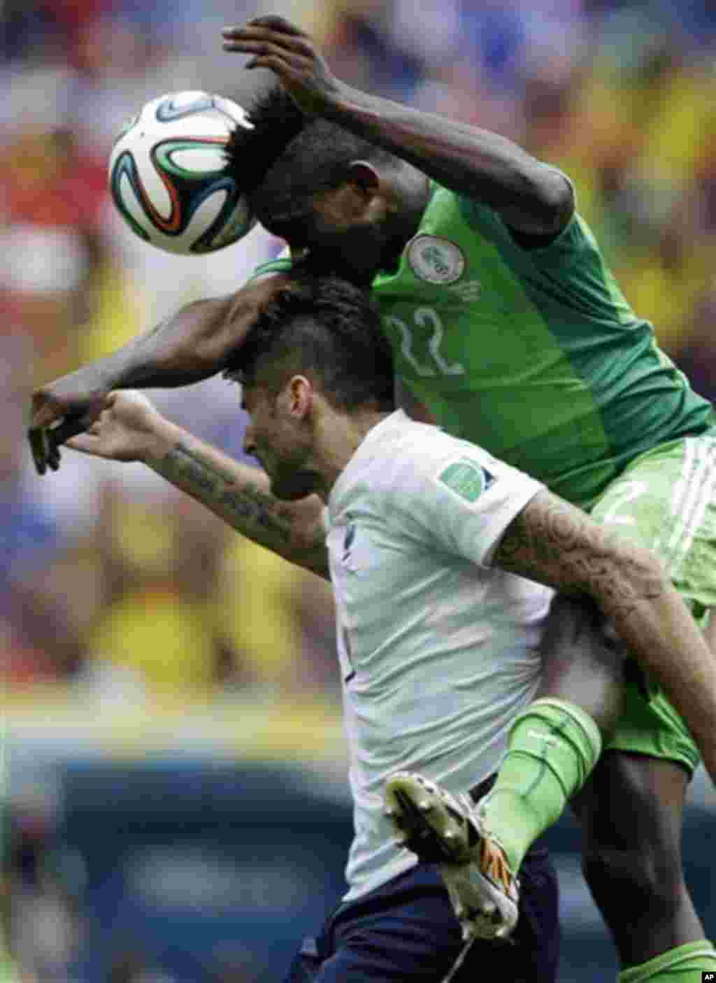 Nigeria's Kenneth Omeruo goes for a header with France's Olivier Giroud during the World Cup round of 16 soccer match between France and Nigeria at the Estadio Nacional in Brasilia, Brazil, Monday, June 30, 2014. (AP Photo/Ricardo Mazalan)