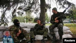 Armed militiamen supporting the self-proclaimed Donetsk People's Republic guard a checkpoint in the eastern Ukrainian city of Donetsk, June 1, 2014.