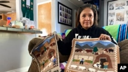 Seraphine Warren poses for a photo in her home in Tooele, Utah, on Sept. 23, 2021, with a rug made by her aunt, Navajo rug weaver Ella Mae Begay.