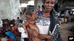 An internally displaced woman holds her malnourished son at a new settlement in Somalia's capital Mogadishu.
