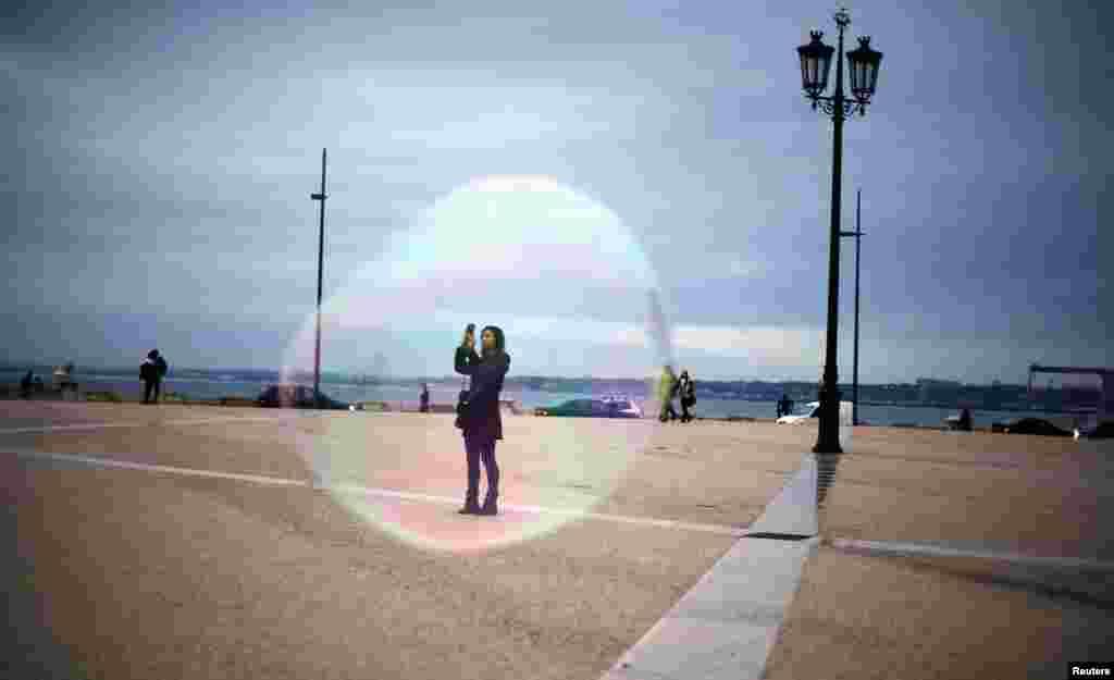 Seorang turis tampak dari sebuah gelembung sabun, sedang mengambil gambar lapangan Comercio di Lisabon, Portugal.