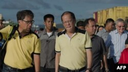 Philippine President Benigno Aquino (R) visits the navy port where some relief supplies arrive by boat in Tacloban, Nov. 17, 2013.