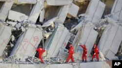 Tim SAR Taiwan berusaha mencari korban di antara reruntuhan gedung berlantai 17 yang ambruk akibat gempa di Tainan, Taiwan, Mingu (7/2).
