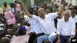 Haiti's presidential candidate Michel Martelly, center, accompanied by fellow candidate Charles-Henri Baker, right, and musician Wyclef Jean ride atop a vehicle through Port-au-Prince to demonstrate against the general elections in Haiti, Sunday, Nov. 28,
