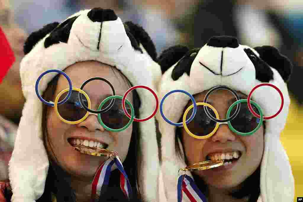Dos espectadoras chinas posan para la foto durante la competencia de Clavados Sincronizados, en el Centro Acuático de Londres.