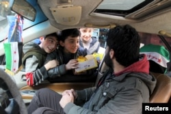 Boys try to sell biscuits to a man driving a car in Aleppo, Syria, March 2, 2016.