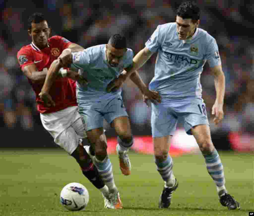 Manchester City's Gael Clichy, centre, and Gareth Barry keep the ball from Manchester United's Nani during their English Premier League soccer match at The Etihad Stadium, Manchester, England, Monday, April 30, 2012. (AP Photo/Jon Super)