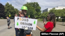 FILE - In this Thursday, June 20, 2019, file photo, a TV reporter interviews self-employed logger Bridger Hasbrouck, of Dallas, Ore., outside the Oregon State House in Salem, Ore.