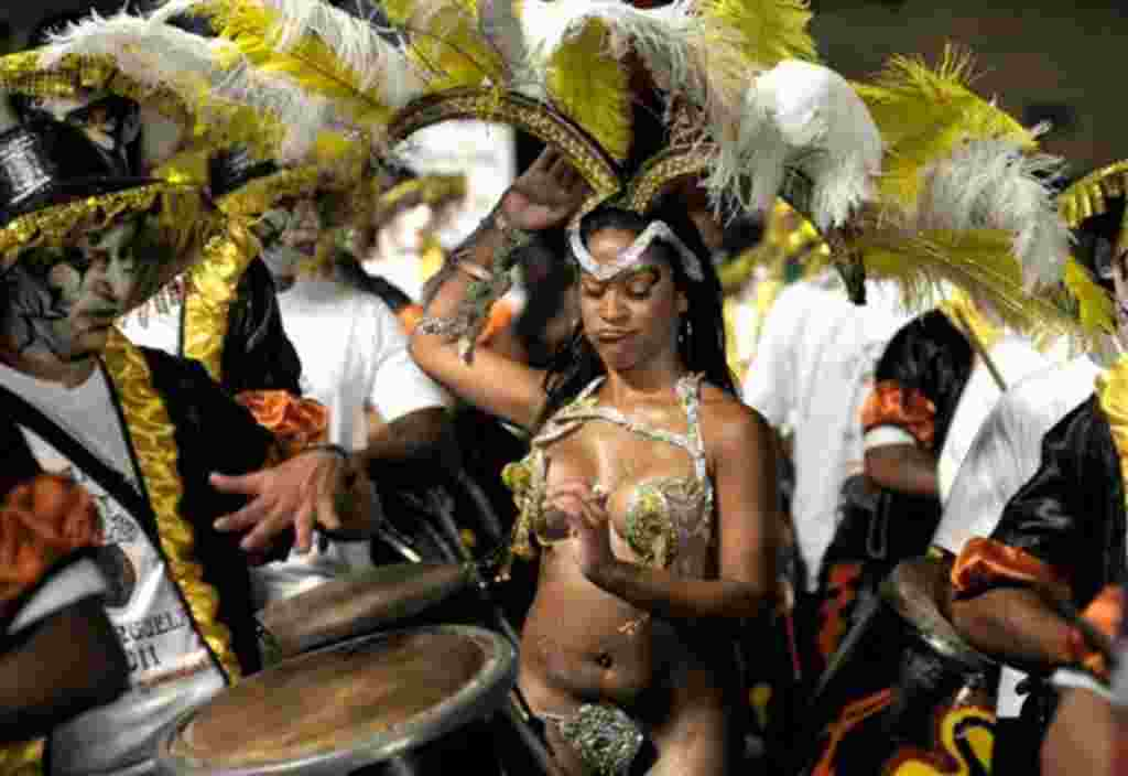 A candombe dancer performs, surrounded by drummers, in the Las Llamadas carnival parade in Montevideo, Uruguay,Thursday, Feb. 3, 2011. (AP Photo/Matilde Campodonico)