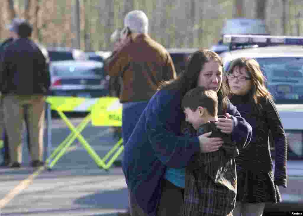 Un niño es abrazado por una persona adulta al salir de la escuela que permaneció bloqueada después del tiroteo.