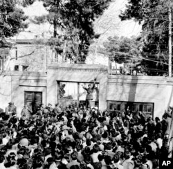FILE- An army officer rallies a crowd of supporters of Shah Mohammed Reza Pahlevi in front of the home of Iranian Prime Minister Mohammed Mossadegh as riots broke out in Tehran, Feb. 28, 1953.