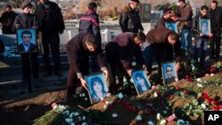 People holds portraits of dead members of the Avetisyan family during a funeral in the city of Gyumri, Armenia, Jan. 15, 2015.