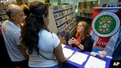 FILE - In this June 24, 2017 photo, Camelia Santiago, administrative assistant with the Puerto Rico Federal Affairs Administration gives out information to a couple during an orientation session for newly arrived Puerto Ricans in Orlando, Fla.