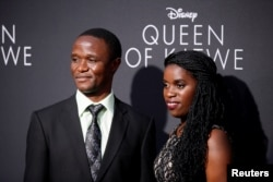 "FILE - Robert Katende (L) and Ugandan chess player Phiona Mutesi (R), who are portrayed in ""Queen of Katwe,"" pose at the film's Los Angeles premiere in Hollywood, California, Sept. 20, 2016."