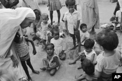 FILE - In this Oct. 25, 1979 file photo, Mother Teresa, left, talks with and blesses the orphans at her Sishu Bhavan (Children's Home) in Kolkata, India.