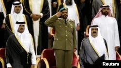 FILE - Qatar's Emir Sheikh Hamad bin Khalifa al-Thani (R) stands next to his son Crown Prince Sheikh Tamim bin Hamad al-Thani before the Emir Cup final match between Al-Sadd and Al-Rayyan at Khalifa stadium in Doha, May 18, 2013.