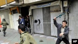 An Iranian opposition protester (l) runs from a member of the security forces with a baton during clashes in Tehran on 27 Dec. 2009.
