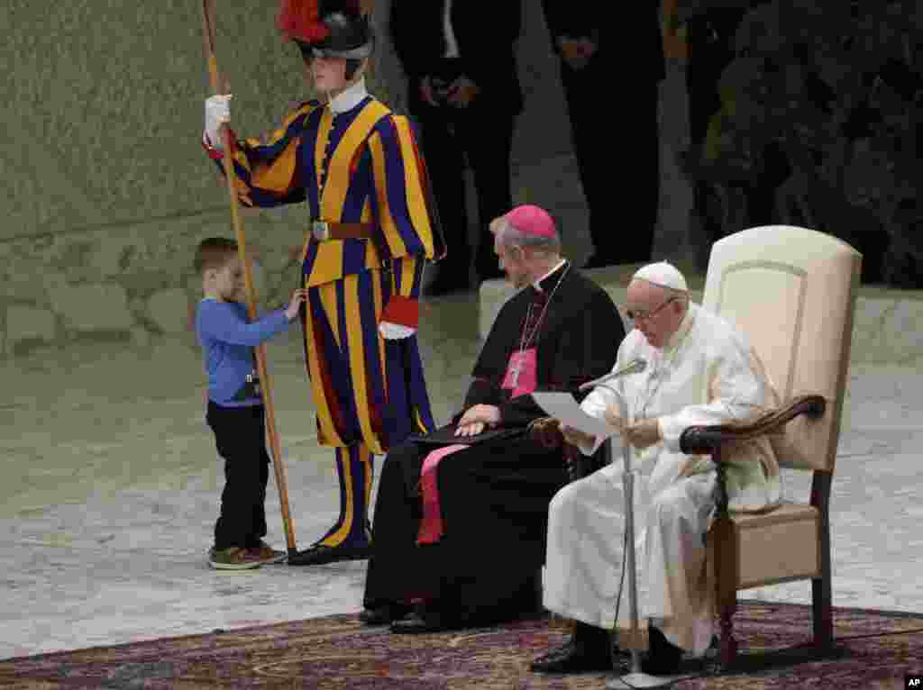 A child plays with a Swiss guard in the Paul VI Hall at the Vatican.