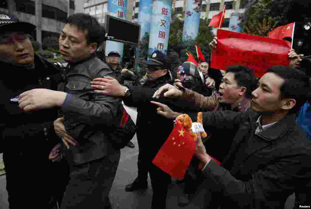 Police separate a supporter of the Southern Weekly from confronting leftists protesting outside the office of the liberal newspaper in the southern Chinese city of Guangzhou, January 9, 2013.