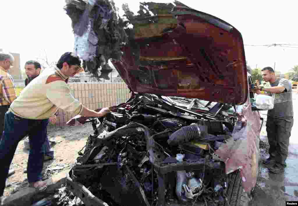 A man inspects a damaged vehicle at the site of bomb attack in Baghdad, March 5, 2014.