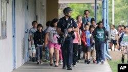 Поліцейський евакуює дітей з місцевої школи.