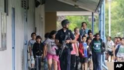 Một cảnh sát viên dẫn đường cho các trẻ em đang trong một cuộc dã ngoại bên ngoài Ðại học Santa Monica, bang California, ngày 7/6/2013.