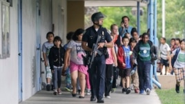 A Santa Monica police officer leads children on a field trip out of Santa Monica College, where they had gone for a planetarium show, following a shooting in the area, in Santa Monica, California, June 7, 2013.