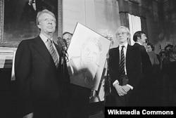 지난 1977년 지미 카터 전 미국 대통령과 앤디워홀이 그린 자신의 초상화를 들고 서 있다.