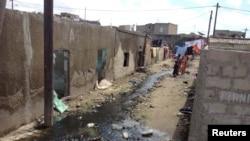 Children walk down an alleyway where sewage runs freely in Pikine, Senegal, Oct. 16, 2015.