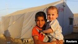 Hai em nhỏ chạy trốn bạo lực ở Mosul đứng bên trong một khu trại tỵ nạn thuộc ngoại ô Arbil, vùng của người Kurd ở Iraq.