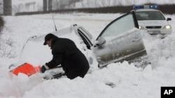 Un homme tente d'enlever la neige couvrant sa voiture près du village de Vetrino, en Bulgarie, pays européen avec le nombre de morts le plus élevé sur les routes, le jeudi 3 janvier 2008.