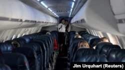 Flight attendants talk in a nearly empty cabin on a Delta Airlines flight operated by SkyWest Airlines as travel has cutback, amid concerns of the coronavirus disease (COVID-19), during a flight departing from Salt Lake City, Utah, U.S. April 11, 2020. RE