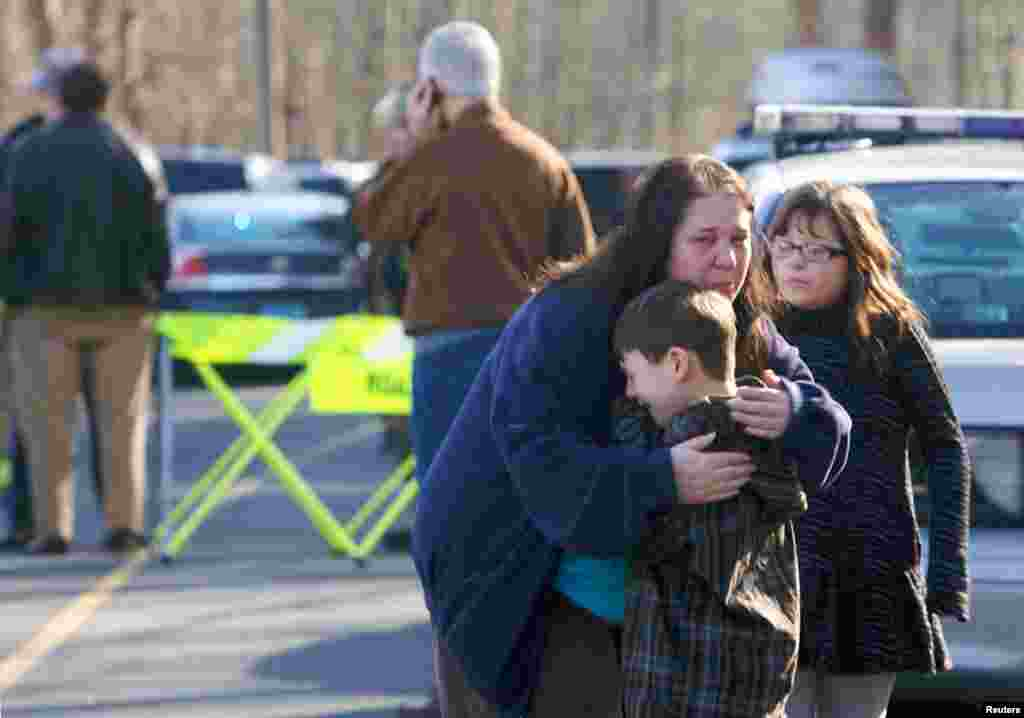 სროლის შემდეგ, დაწყებითი სკოლის მოსწავლე თვითმხილველ ბიჭუნას ამშვიდებენ ოჯახის წევრები, 14 დეკემბერი, 2012.