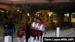 In this Feb. 8, 2020, photo, two women wearing traditional Mexican dresses walk by during the celebration of the town's 45th year since it was incorporated in Guadalupe, Ariz.