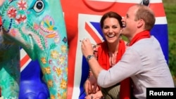 Britain's Prince William decorates an Elephant Parade statue as his wife Catherine, the Duchess of Cambridge, laughs during a visit to the Mark Shand Foundation at Kaziranga in the northeastern state of Assam, India, April 13, 2016.